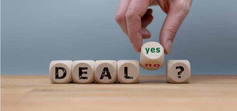 """Deal or no deal? Hand turns a cube and changes the word """"no"""" to """"yes""""."""