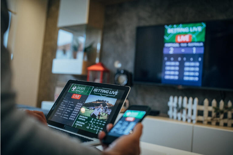 Man watches soccer game and bets in his living room