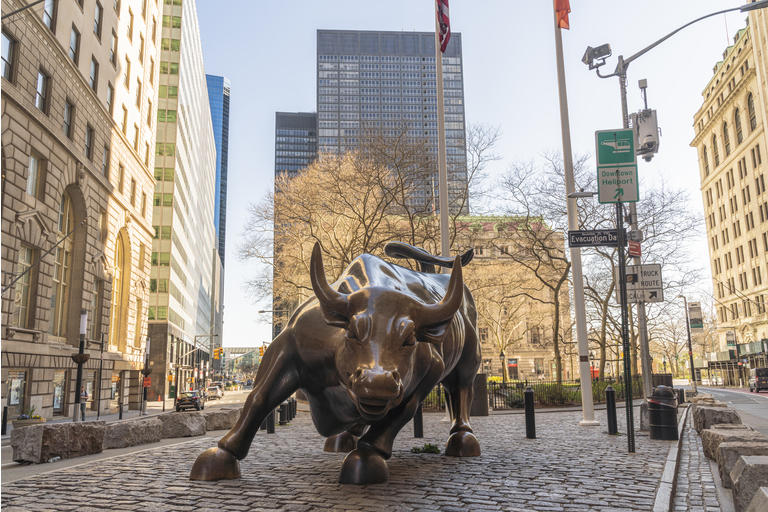 The iconic Charging Bull statue is not surrounded by the usual crowd because the city is deserted during the state of emergency triggered by the COVID-19 pandemic.