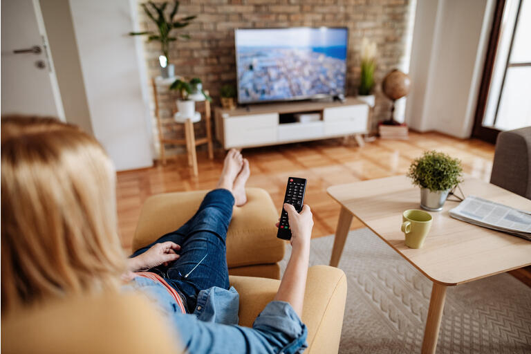 Barefoot mature woman relaxing at home and watching TV