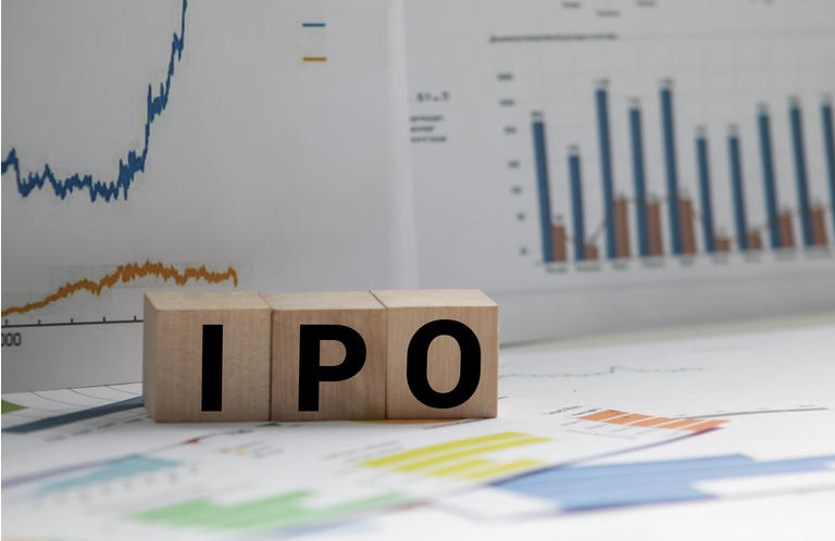 A Notebook with Business notes initial coin offering ICO vs IPO Initial Public Offering with office tools on yellow blue background. Concept of the choice of IPO or ICO