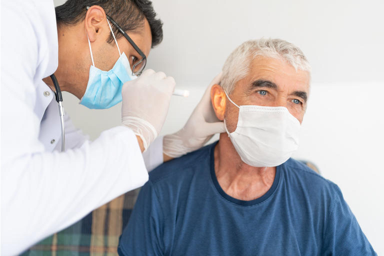 Health worker examine ear of senior man in his house