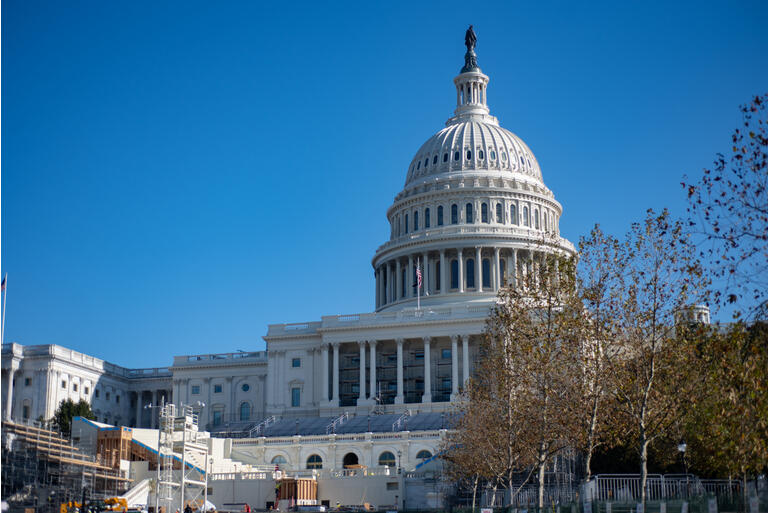 The United States Capitol Building, preparing construction for inauguration on blue sky background.