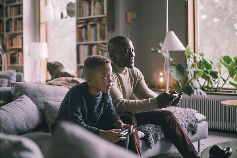 Smiling father and son playing video game while sitting on sofa at home