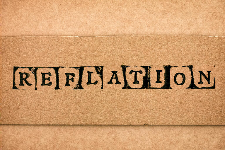 Cardboard with word Reflation made by black alphabet stamps.