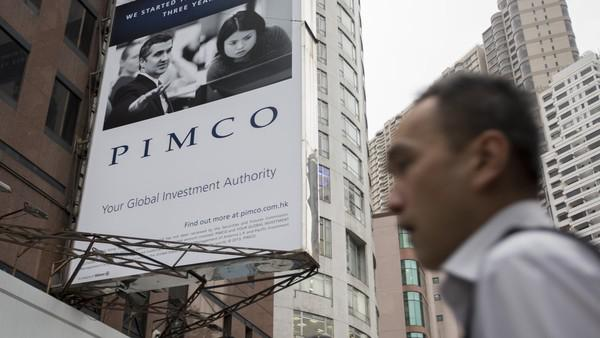A man walks past a Pacific Investment Management Company LLC (PIMCO) advertisment which is displayed on a building in Hong Kong, China, on Wednesday, Nov. 13, 2013. Pacific Investment Management Co.