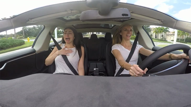 Screen capture of two women in a Tesla, via Bing.