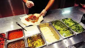 Chipotle employee preparing a burrito.