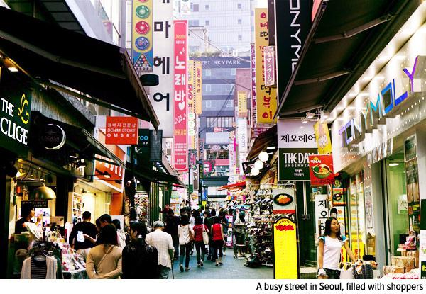 A busy street in Seoul, filled with shoppers.