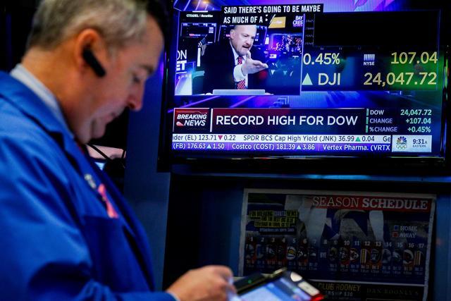 Traders work on the floor of the New York Stock Exchange, (NYSE) as a screen displays the Dow Jones Industrial Average as it crosses 24,000, in New York, U.S., November 30, 2017. REUTERS/Brendan McDermid
