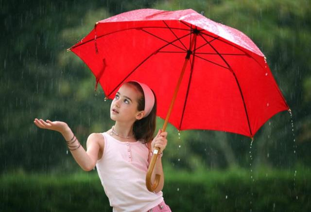 A person holding a red umbrella Description generated with very high confidence