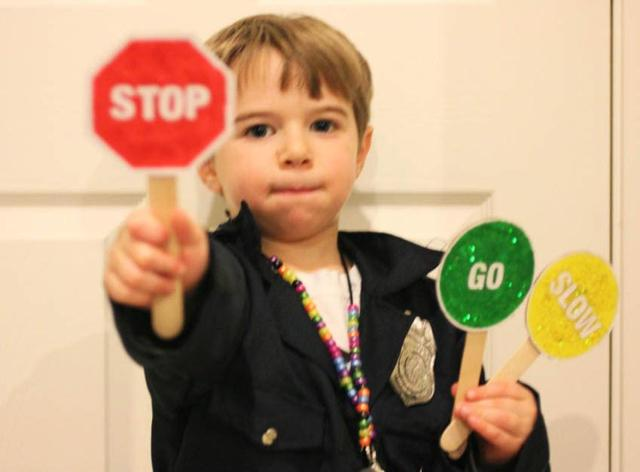 A young boy holding a sign posing for the camera Description generated with high confidence