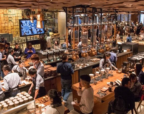 Baristas make drinks for customers in the middle of the new Starbucks Reserve Roastery in Shanghai.