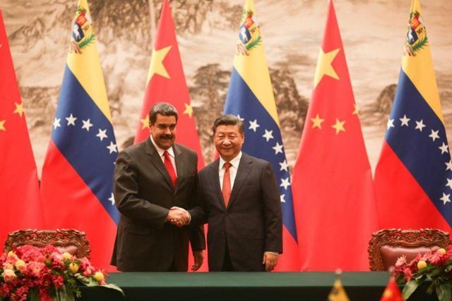 Venezuelan President Maduro (<span>L</span>) shakes the hand of Chinese President Xi Jinping during his state visit to China