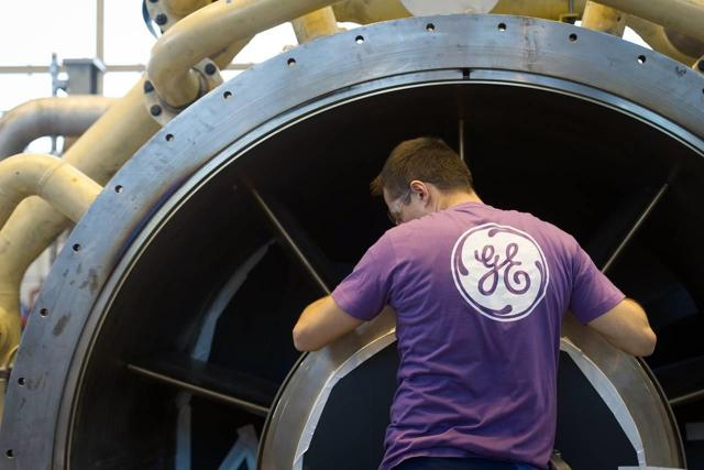 GE employee works on a gas turbine in France. Source: Barron