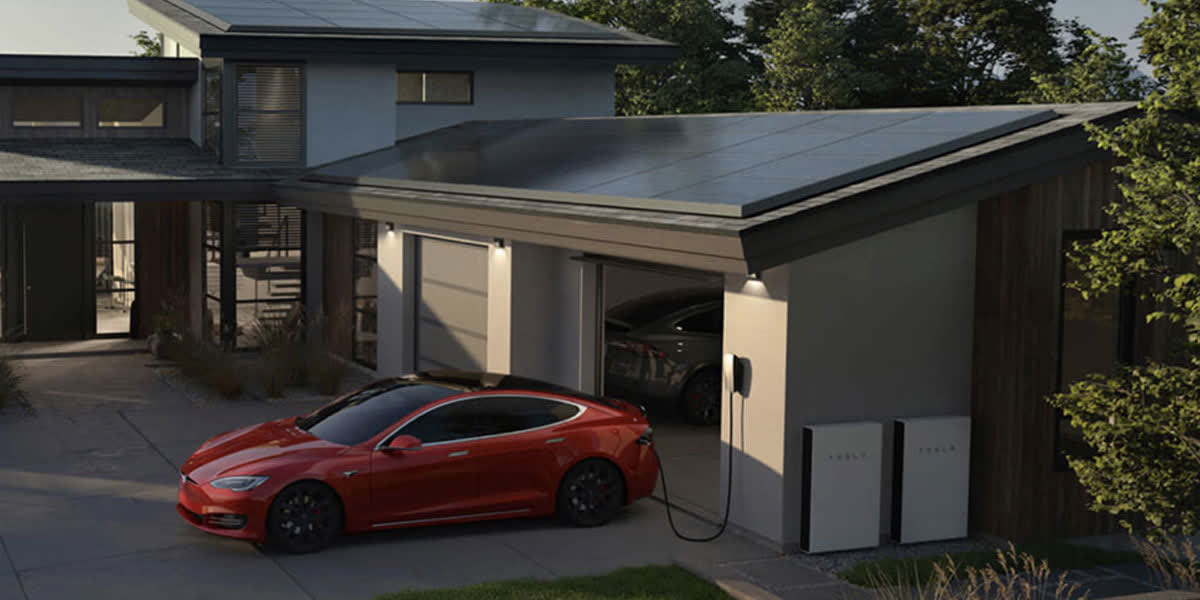 A close up of a home and garage with Tesla solar panels, Tesla Powerwall batteries and a red Tesla car in the driveway